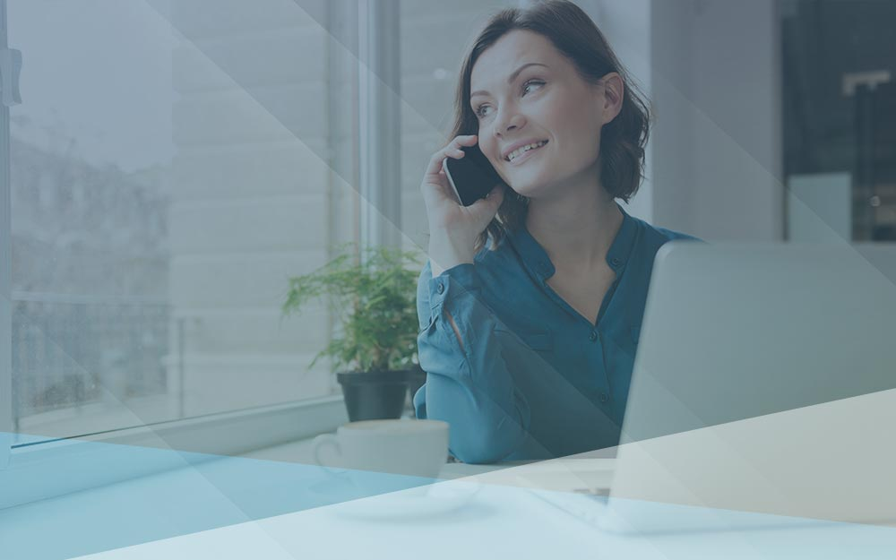 Smiling women talking on the phone and using laptop.