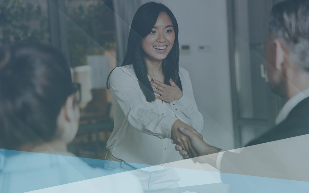Hiring manager shakes hand with smiling female