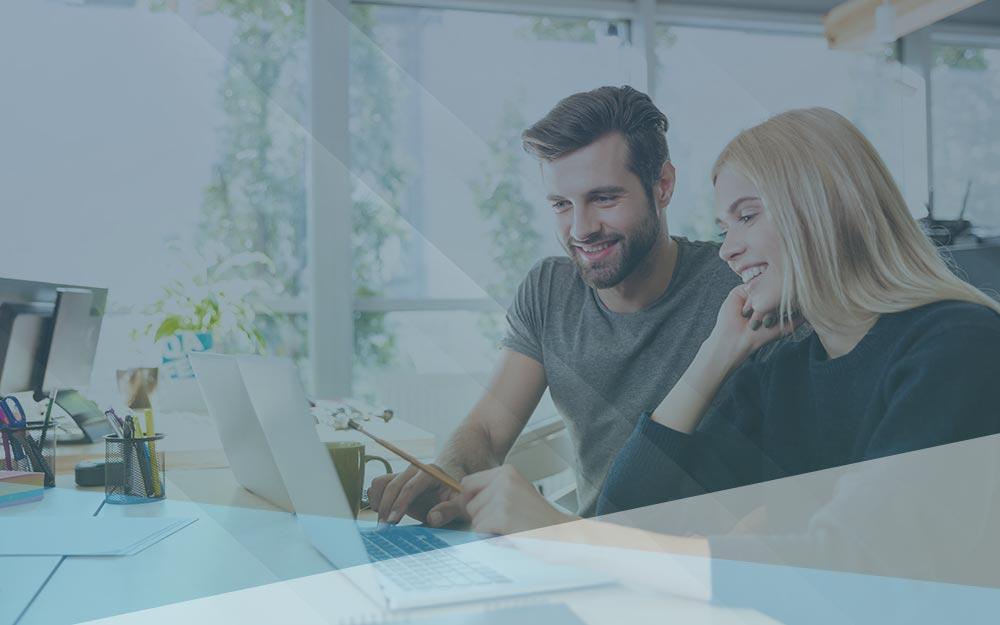 Smiling man and women work at laptop.