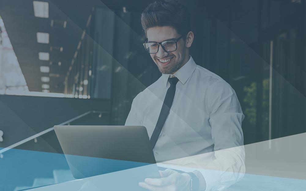 Smiling man with glasses working at laptop.