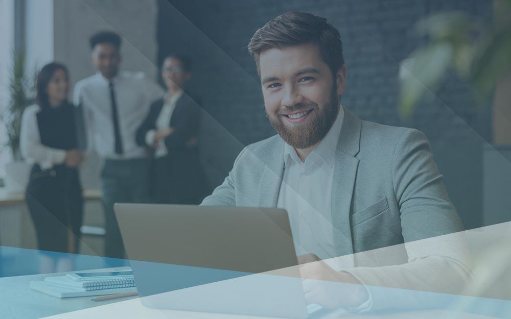 Smiling man working at laptop.