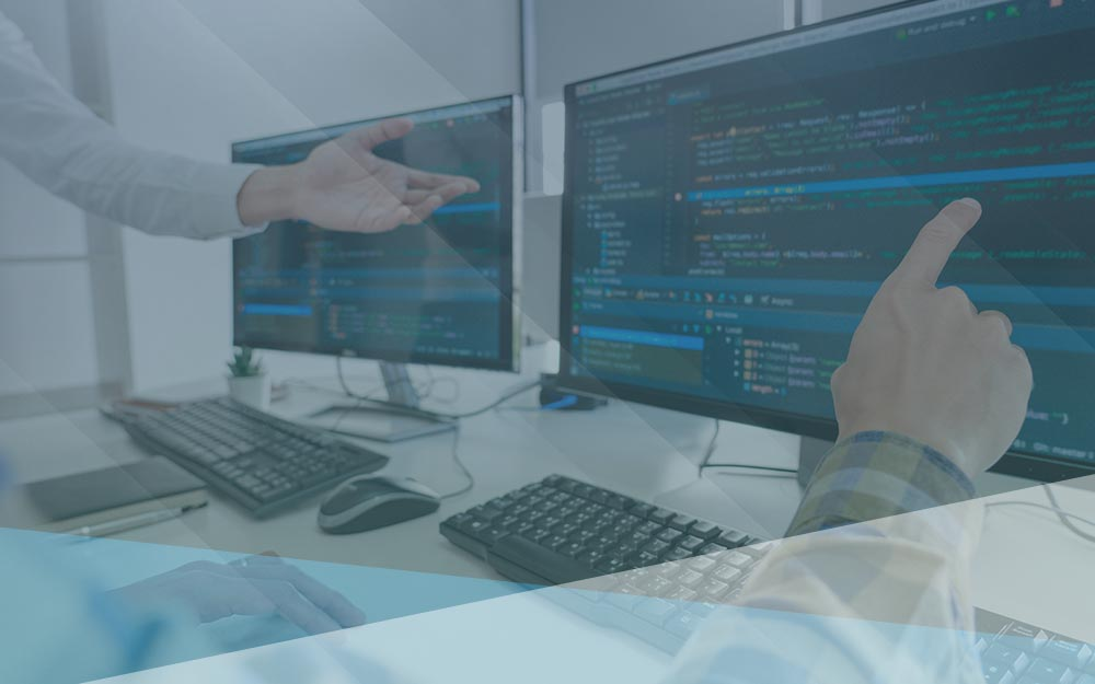 Workers sit at desk at point to software coding language on screen.