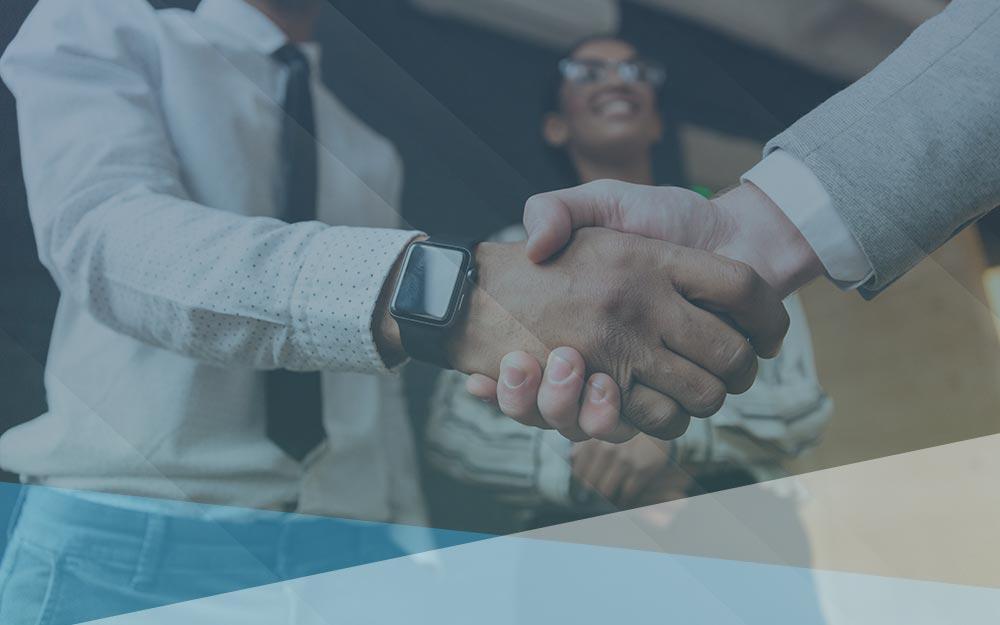"Two men shaking hands"">."