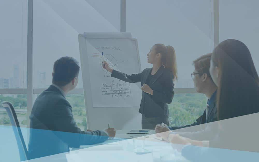 Businesswoman pointing at whiteboard and giving her colleagues business training